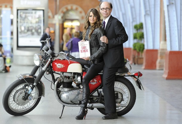"Thriller writer Jeffery Deaver poses for photographers with model motorbike to launch the new James Bond book ""Carte Blanche"" at St Pancras station in London"